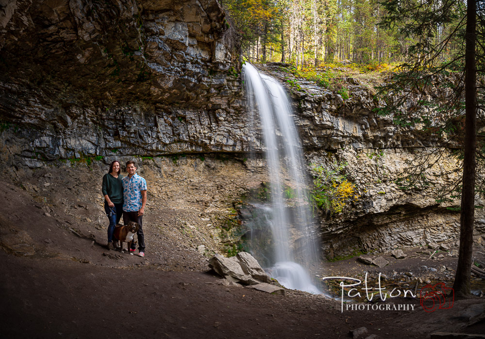 Engagement photograph of a couple under a waterfall