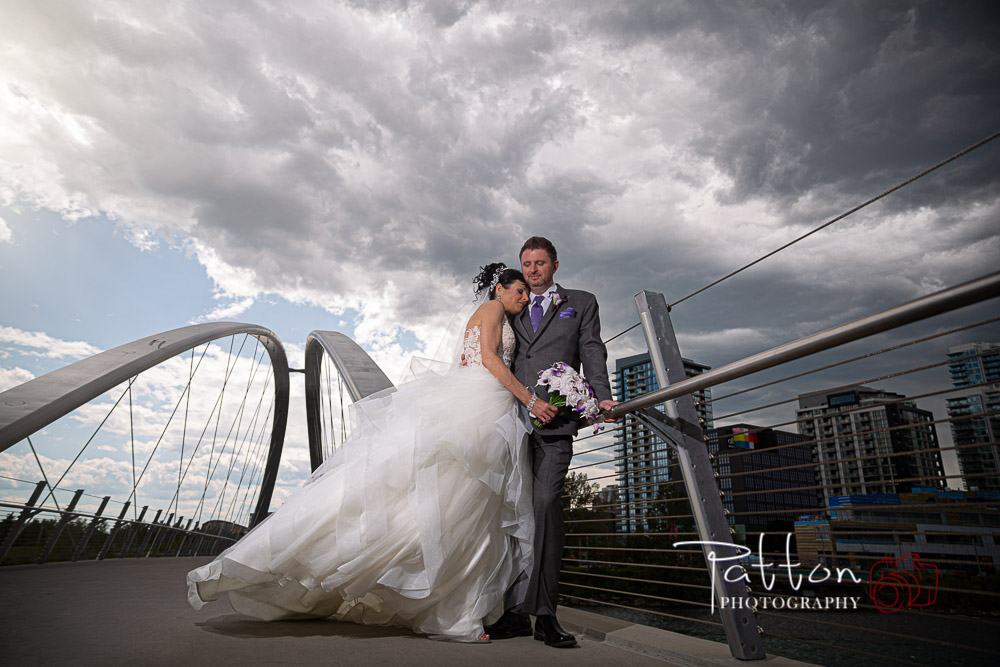 Bride and groom on bridge with dramatic sky