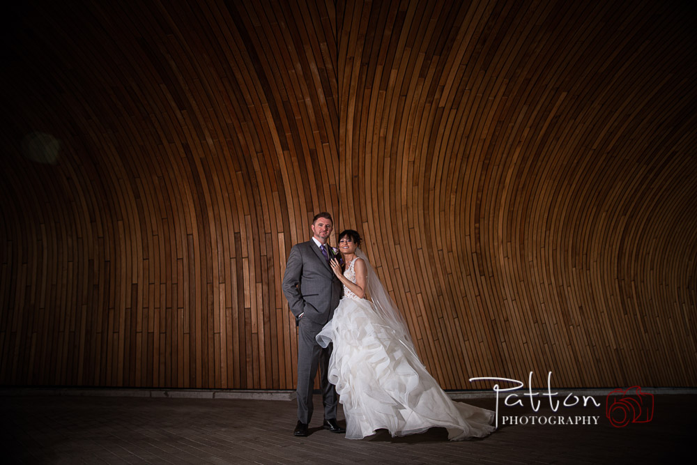 Calgary bride and groom in front of curved wooden wall
