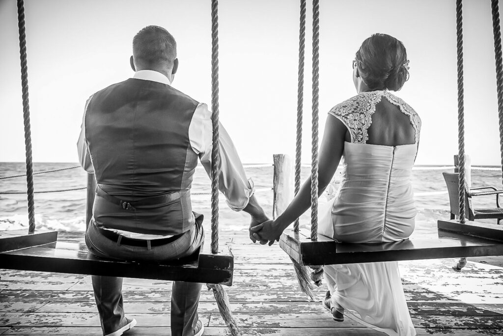 Bride and groom at a destination wedding holding hands on swing