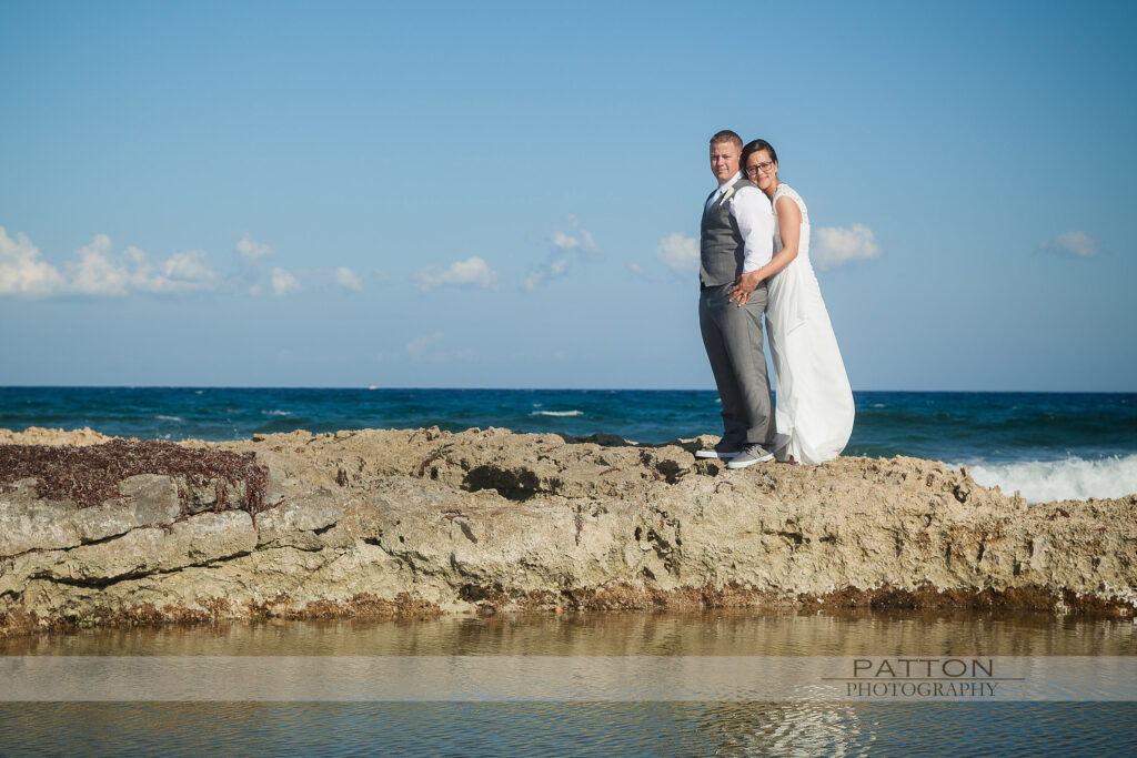Bride and Groom standing on rocks at a destination wedding